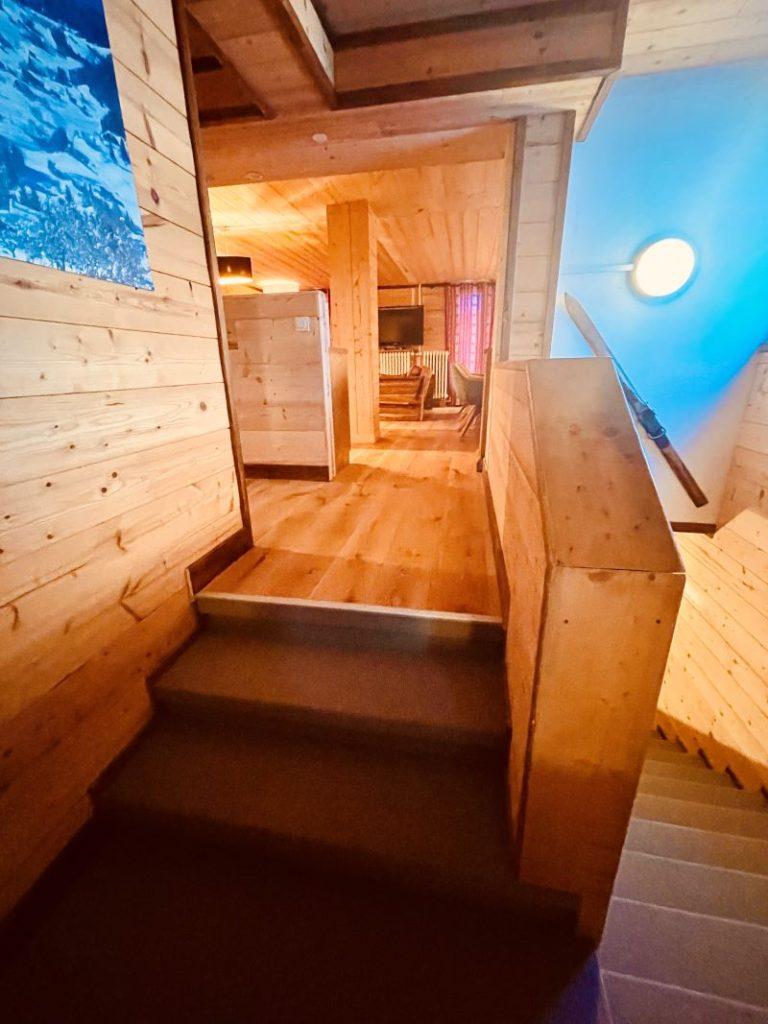 Arrivée à l'étage de l'appartement Alpe à l'Alpe d'Huez menant au 1er étage avec toutes les chambres et la belle pièce de vie au charme typique Bois montagne