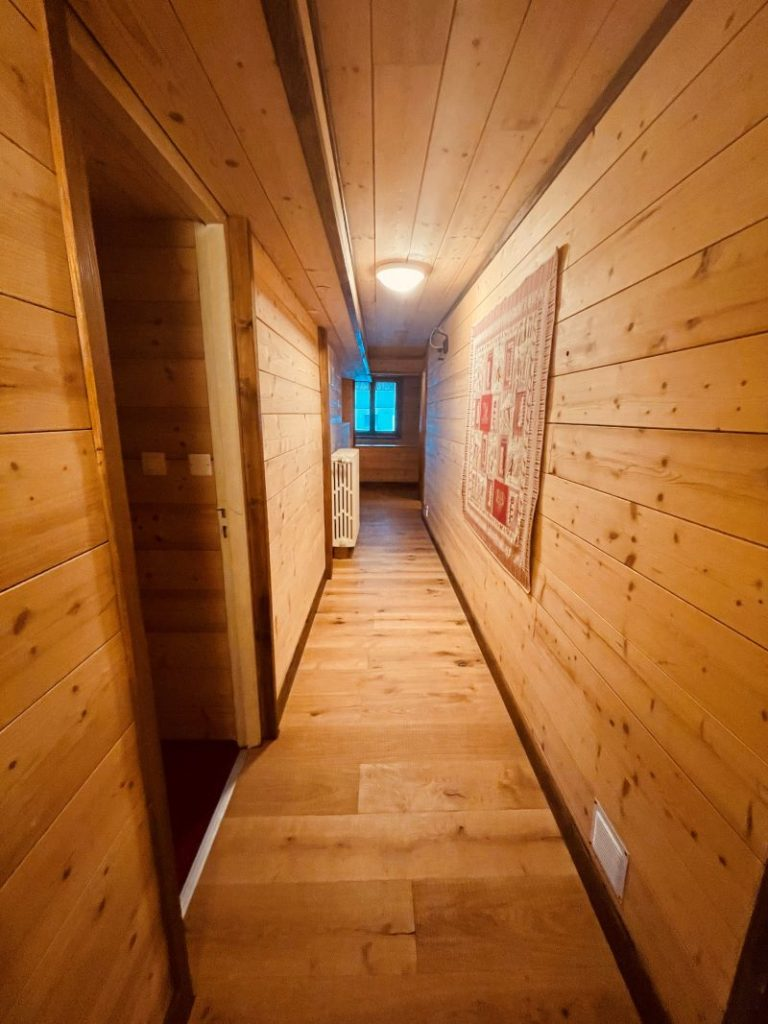 Large corridor with the typical charm of the mountain woods leading to the rooms of l'apartment Alpe at l'Alpe d'Huez