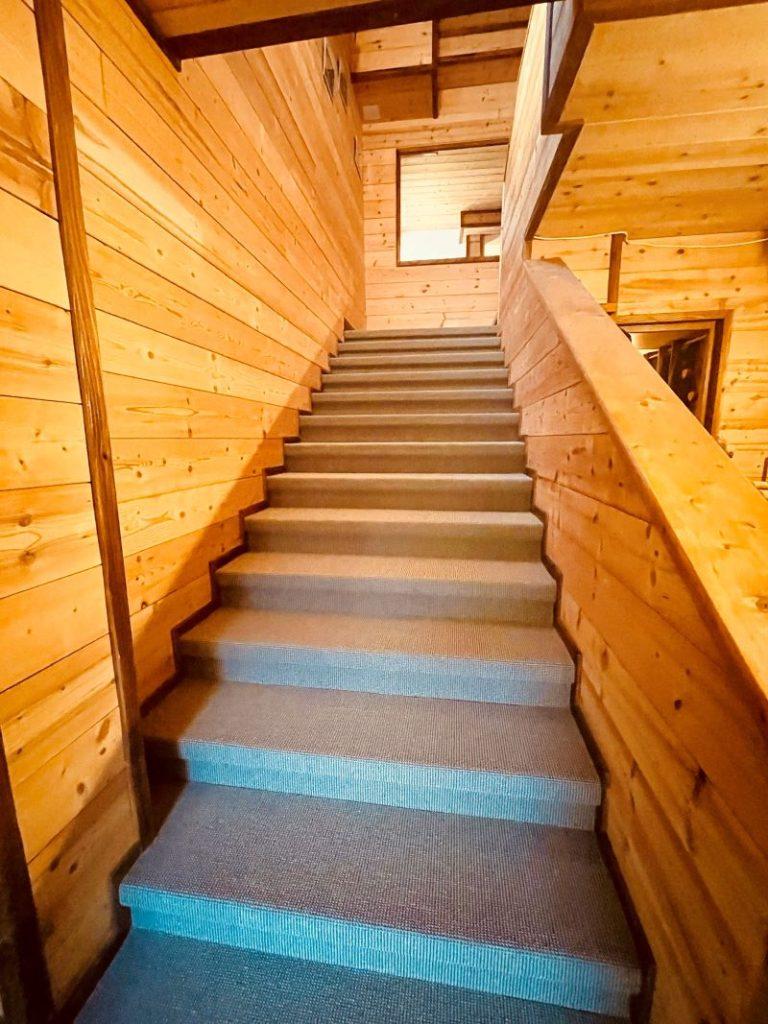 Escalier de l'appartement Alpe à l'Alpe d'Huez menant au 1er étage avec l'espace spa à droite de l'escalier au rez-de-chaussée