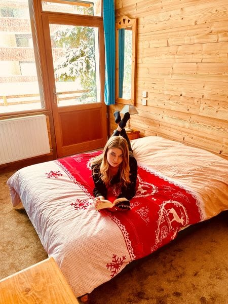 Amandine leyendo en la cama de la muy Hermosa Habitación 1 auténtica montaña de l'Huez apartamento en l'Alpe d'Huez 1850 M en el centro de la estación