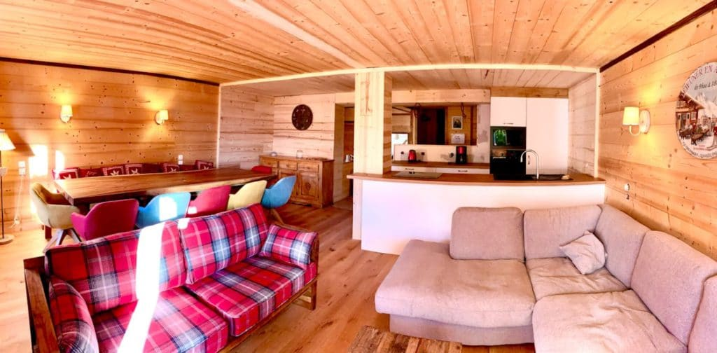 The beautiful living room, authentic mountain wood atmosphere, with comfortable living room, very nice wooden table welcoming 12 guests and kitchen open to the living room of l'appartement Alpe à l'alpe d'Huez, at the foot of the slopes and in the heart of the resort
