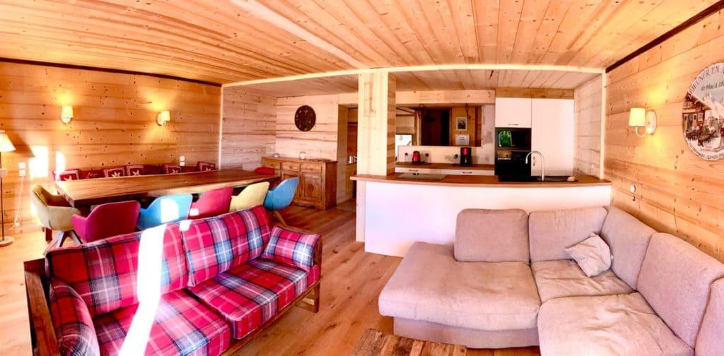 La belle pièce de vie, ambiance authentique bois de montagne, avec salon confortable, très belle table en bois accueillant 12 convives et cuisine ouverte sur le séjour de l'appartement Alpe à l'alpe d'Huez, au pied des pistes et au cœur de la station