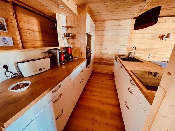 Très belle cuisine toute neuve et tout équipée, ambiance bois, typique montagne, ouvert sur le séjour donnant sur un balcon de l'appartement Alpe à l'Alpe d'Huez au 1er étage, proche des pistes et du centre bourg de la station