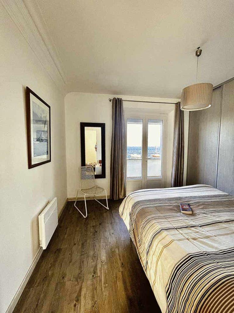 Zimmer 2 der Villa Bord de Mer auf der Presqu'île de Giens mit einem Doppelbett 160, mit Blick auf einen Balkon und einen riesigen Blick auf das Meer und die Boote.