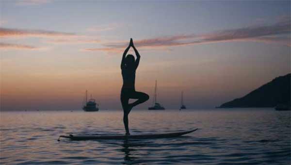 une très belle femme faisant du yaga sur un paddle sur une mer plate au coucher du soleil