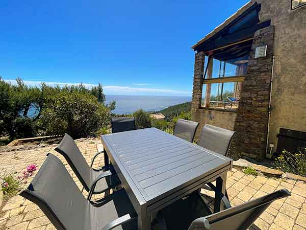 Magnifique terrasse avec table et chaise pour y déjeuner ou y dîner de la maison Villa vue mer en plein après midi, avec un temps très ensoleillé